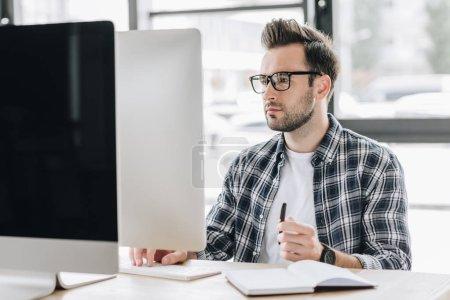 Photo pour Jeune homme concentré dans les lunettes de travail avec ordinateur de bureau - image libre de droit