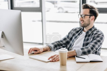 smiling young man in eyeglasses using desktop computer at workplace