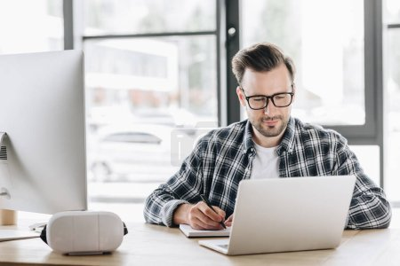 handsome young programmer in eyeglasses taking notes while working with laptop and desktop computer