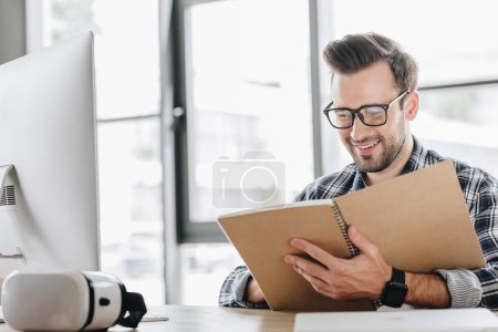 smiling young man in eyeglasses writing in notebook at workplace