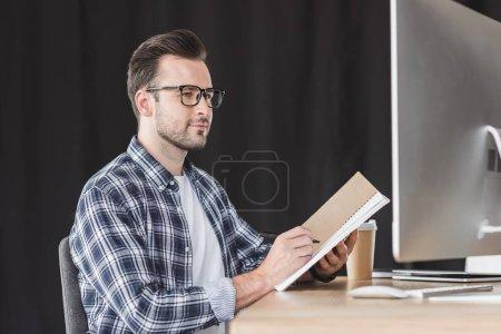 Photo pour Beau jeune programmeur en lunettes, prendre des notes dans l'ordinateur portable et à l'aide d'ordinateur de bureau - image libre de droit