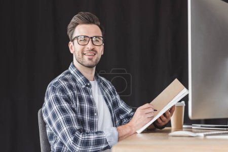 handsome young man in eyeglasses taking notes in notebook and smiling at camera while sitting at workplace