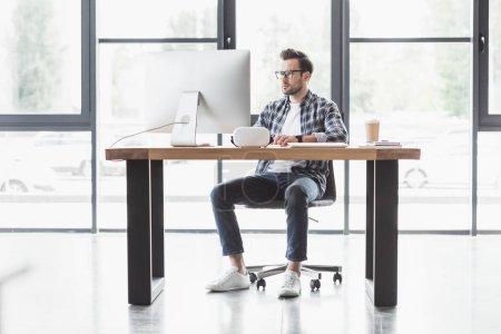 Photo pour Vue complète du beau jeune programmeur utilisant un ordinateur de bureau sur le lieu de travail - image libre de droit