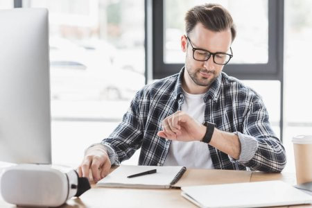 young man in eyeglasses checking smartwatch while sitting at workplace