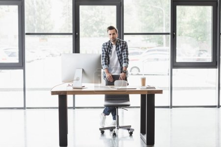 handsome young programmer looking at camera while standing at workplace