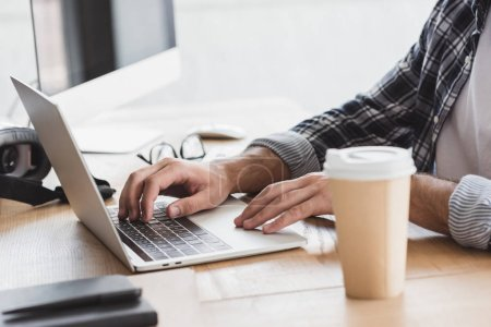 Photo for Close-up partial view of young man using laptop at workplace - Royalty Free Image