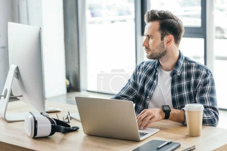 Photo for Handsome young programmer using laptop and desktop computer at workplace - Royalty Free Image
