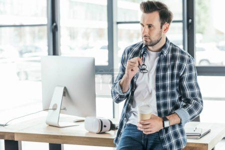 young man holding coffee to go and looking away while sitting on table with desktop computer