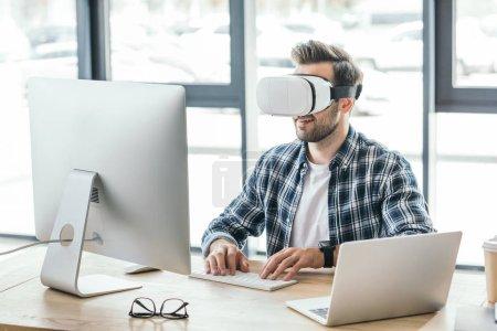 Photo pour Jeune homme en réalité virtuelle casque en utilisant ordinateur de bureau et ordinateur portable sur le lieu de travail - image libre de droit