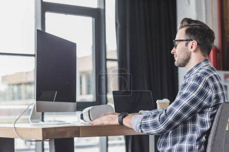 Photo pour Beau sourire jeune programmeur en lunettes de travail avec ordinateur portable et ordinateur de bureau - image libre de droit