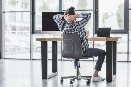 back view of young programmer sitting with hands behind head at workplace