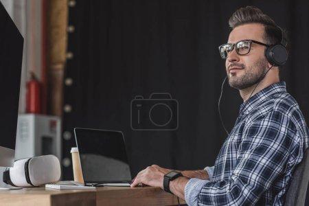 Photo pour Jeune homme souriant dans les lunettes et les écouteurs de travail avec ordinateur portable - image libre de droit