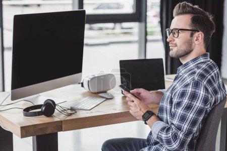 Photo pour Jeune homme souriant dans les lunettes à l'aide d'un smartphone et en regardant loin sur le lieu de travail - image libre de droit