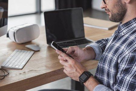 Schnappschuss eines lächelnden Mannes mit Smartphone am Arbeitsplatz