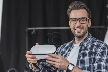 Photo for Handsome young man in eyeglasses holding virtual reality headset and smiling at camera - Royalty Free Image