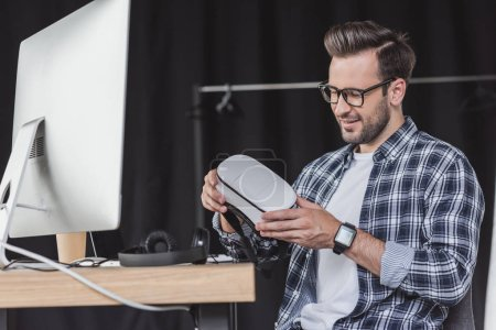 smiling young man in eyeglasses holding virtual reality headset at workplace