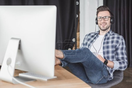 smiling young man in headphones and eyeglasses looking at desktop computer