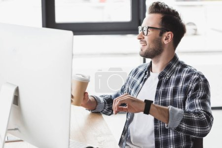 handsome smiling young programmer in eyeglasses holding paper cup while working with desktop computer