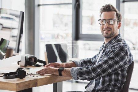 schöner junger Mann mit Brille, der während der Arbeit mit Desktop-Computer und Laptop in die Kamera lächelt
