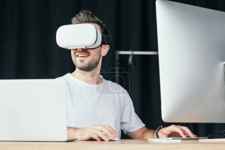 smiling young man in virtual reality headset using desktop computer and laptop