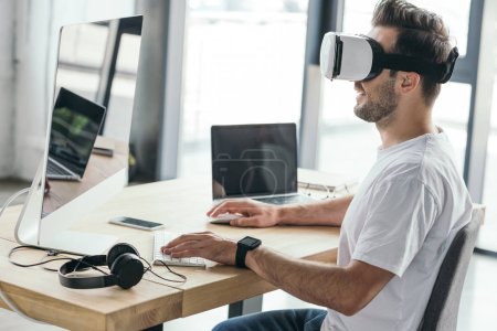 smiling young man in virtual reality headset using desktop computer at workplace