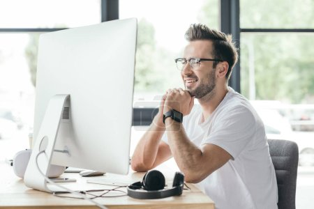 Photo for Smiling young programmer in eyeglasses using desktop computer at workplace - Royalty Free Image