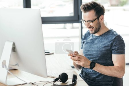 smiling young man in eyeglasses using smartphone while sitting at workplace with desktop computer