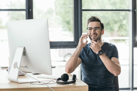 handsome smiling young man in eyeglasses talking by smartphone while working with desktop computer