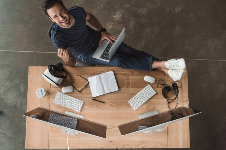 Photo for Overhead view of handsome young programmer using laptop and smiling at camera - Royalty Free Image