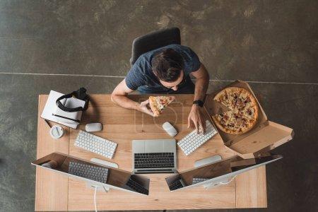 Photo pour Vue aérienne du programmeur mangeant de la pizza et utilisant des ordinateurs sur le lieu de travail - image libre de droit