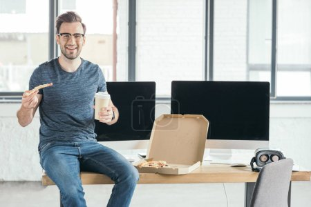 smiling young programmer in eyeglasses holding paper cup and eating pizza at workplace