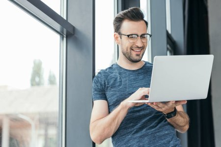 smiling young man in eyeglasses using laptop near window