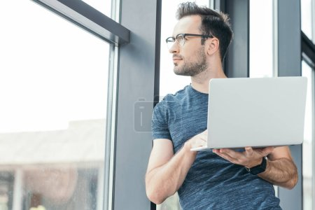 handsome young man in eyeglasses holding laptop and looking at window