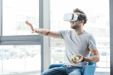 Photo pour Heureux jeune homme en réalité virtuelle casque tenant pomme et assis sur la chaise - image libre de droit