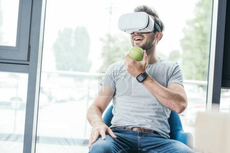 smiling young man holding green apple and using virtual reality headset