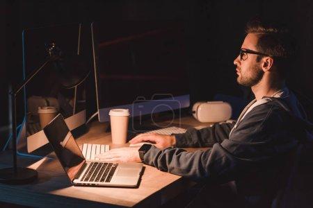 Photo pour Vue latérale du jeune programmeur en lunettes travaillant avec des ordinateurs portables et de bureau pendant la nuit - image libre de droit