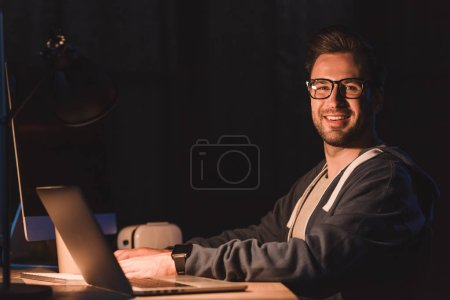 handsome young programmer in eyeglasses smiling at camera while working with laptop and desktop computer at night time