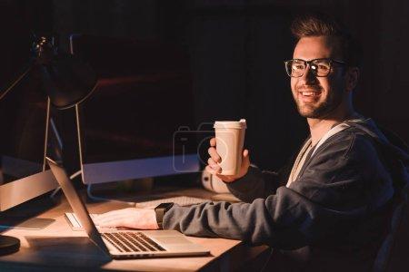 Photo pour Souriante jeune programmeur en lunettes tenant café pour aller tout en travaillant avec des ordinateurs portables et de bureau - image libre de droit
