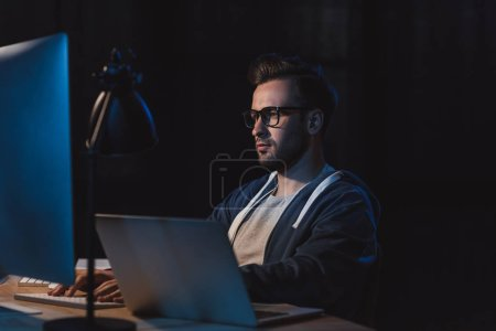 Photo for Young programmer in eyeglasses working with desktop computer and laptop at night - Royalty Free Image