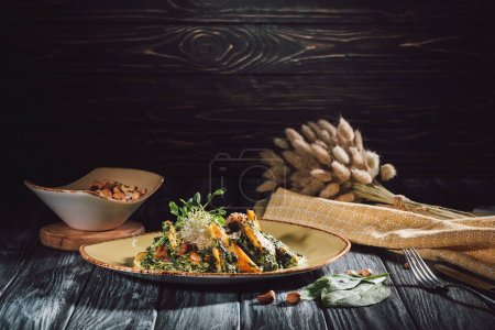 food composition of panikesh with spinach and bowl with cashew nuts on wooden table