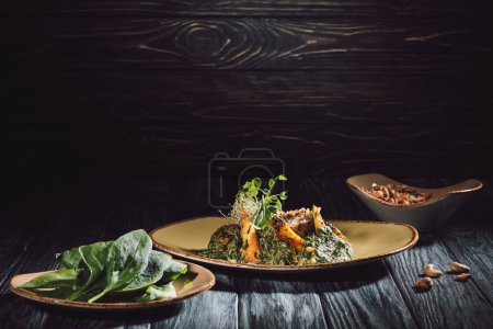 Photo for Plates with spinach leaves and panikesh near bowl with cashew nuts on wooden table - Royalty Free Image
