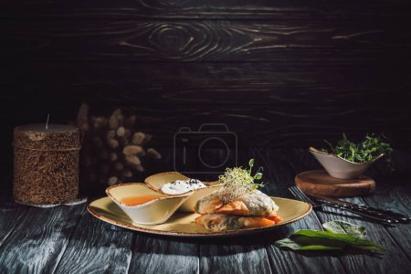 Photo for Food composition of candle and samosas in phyllo dough stuffed with spinach and paneer decorated with germinated seeds of alfalfa and sunflower on plate with sauces - Royalty Free Image