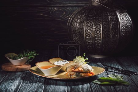Photo for Food composition of candle and samosas in phyllo dough stuffed with spinach and paneer decorated with germinated seeds of alfalfa and sunflower - Royalty Free Image