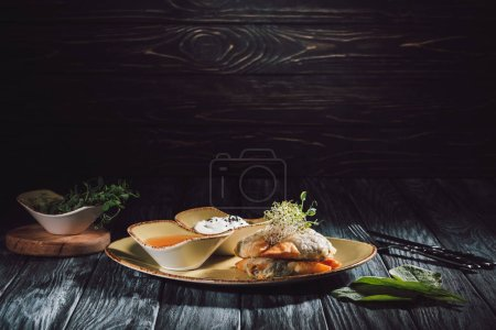 Photo for Samosas in phyllo dough stuffed with spinach and paneer decorated with germinated seeds of alfalfa and sunflower on plate with sauces - Royalty Free Image