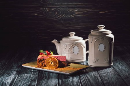 carrot cake with berry filling on plate and teapot on wooden table