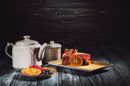 carrot cake with berry filling on plate, orange slices, blueberries and cranberries on saucer near teapot on wooden table
