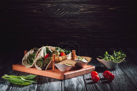 Photo for Food composition of tortillas with falafel, cherry tomatoes and germinated seeds of sunflower on wooden tray with sauces on table - Royalty Free Image
