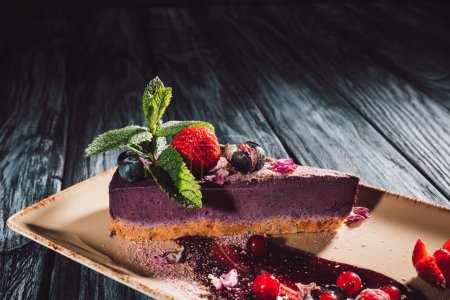 close up view of blueberry cake with strawberries, mint and viola petals on plate on wooden table