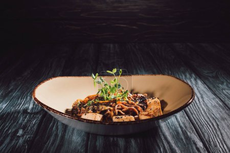 Photo for Soba with tofu and vegetables decorated with germinated seeds of sunflower on plate on wooden table - Royalty Free Image