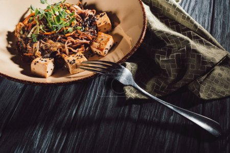 Photo for High angle view of soba with tofu and vegetables decorated with germinated seeds of sunflower on plate near kitchen towel and fork on wooden table - Royalty Free Image
